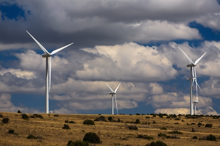 View of wind turbines on a plain with a dramatic cloudy sky. photo