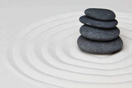 Close-up van een stapel stenen op raked zand in een Japans decoratieve of zen-tuin. Stockfoto