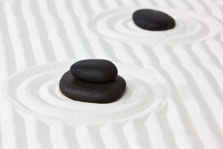 Close-up of black stones on white raked sand in a Japanese ornamental or zen garden. photo