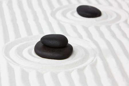 raked: Close-up of black stones on white raked sand in a Japanese ornamental or zen garden. Stock Photo