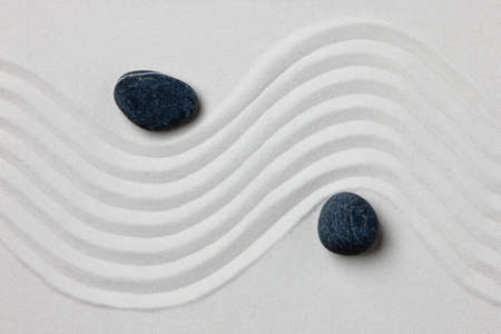 Close-up of two stones on white raked sand in a Japanese ornamental or zen garden. Stock Photo
