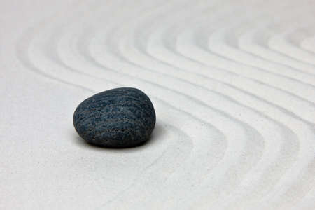 waves  pebble: Close-up of a stone on white raked sand in a Japanese ornamental or zen garden. Stock Photo