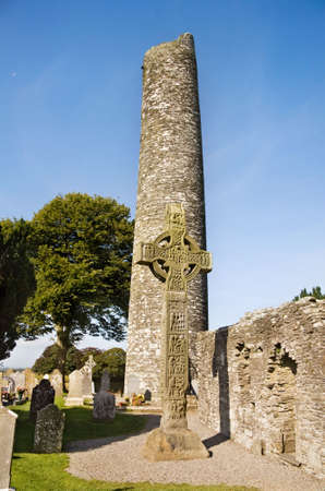 monastic: Fifth century monastic settlement at Monasterboice, county Louth in Ireland. View over the round tower and the Western High Cross. At over 6.5 m high this is the tallest celtic High Cross in Ireland.  Stock Photo