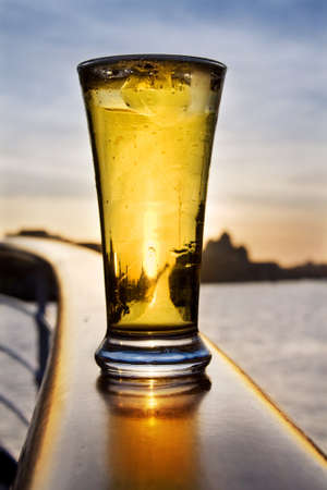 Pint of iced cold beer at sunset on a ship. Over Dublin skyline.  photo
