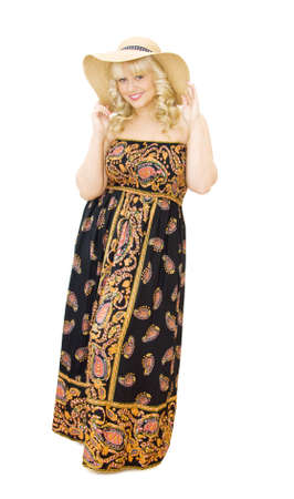 maxi dress: Summer vacations - beautiful young woman wearing straw hat and paisley pattern strapless dress. She is smiling and getting ready to have fun. Isolated over white background.
