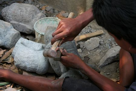 Asian man carving a stone Buddha head