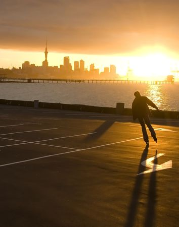 active arrow: Silhouette of a roller at a sunset, Auckland city