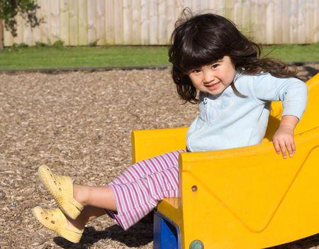 Little girl smiling and sliding on children's chute Stock Photo - 2043063