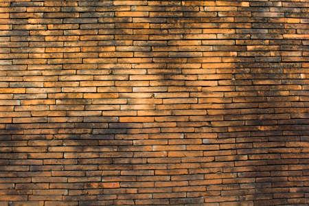 dark brick wall texture in basement house interior with beam of light photo