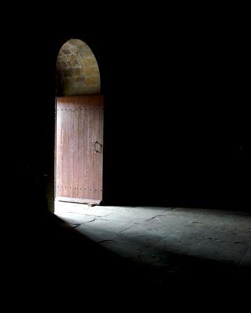 creepy monster: La luce entra in una stanza buia attraverso una porta in un antico cattedrale.