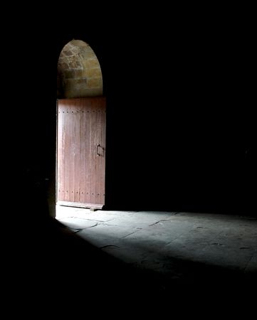 suspense: Light entering a dark room through a door in an ancient cathedral.