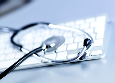 it support: Selective focus of a stethoscope lying on a computer keyboard. Research or technical support theme. IT support. Stock Photo