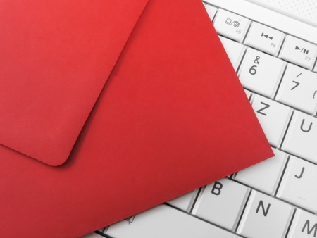 red envelope: Red envelope and white keypad. Email, envelope and white laptop