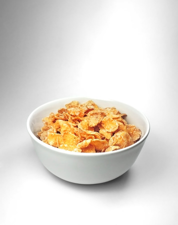 cornflakes: Cornflakes in a bowl, isolated on white and gray background