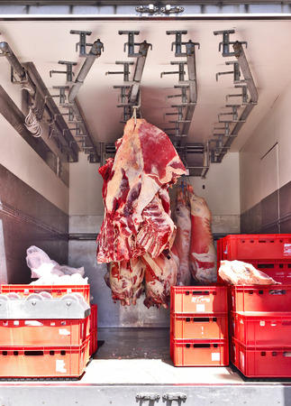 perishable: Raw beef butchery, transport. Raw meat hanging on meat hooks in a truck.