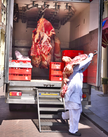 Raw beef butchery, transport. Raw meat hanging on meat hooks in a truck.