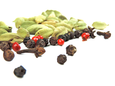 peppercorns: Spices on white. Peppercorns, cardamom and cloves. Stock Photo