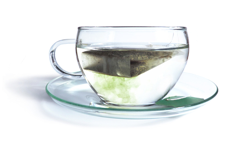 assam tea: Green tea with tea bag, coloring the hot water. Isolated on White