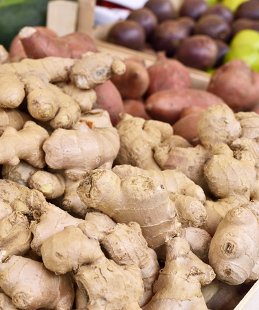 market stall: Fresh ginger at a market stall. Weekly marketplace with fresh vegetables and fruits. Selective focus of ginger in a wooden box at a market stall. Stock Photo