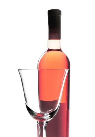 rose wine: Rose wine bottle and empty red wine glass. Stock Photo