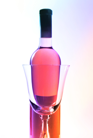 Rose wine bottle and empty red wine glass. Color filter.