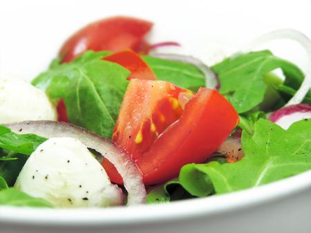 rukola: Fresh salad with arugula, tomatoes, red onions and mozzarella. Stock Photo