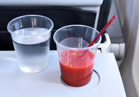 Drinks on a flight. Tomato juice and water glass on a table in airplane at.