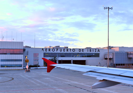 looking through an object: Aiport of Ibiza Iceland in the sunset. View outside the airplane window to the airport building.