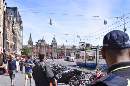 urban scene: Amsterdam, Netherlands - June 15, 2015: Amsterdam Centraal Station. Building exterior of Amsterdam Centraal and blue sky. Capital city of the Netherlands, central station or metro station.