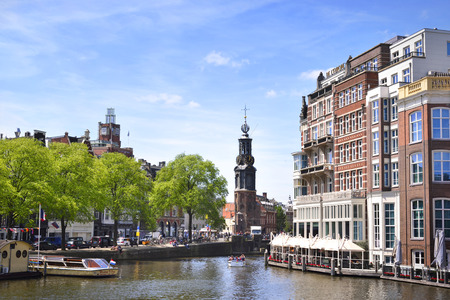 tour boats: Canal at Amsterdam city, Netherlands. Excursion boats and cityscape of Amsterdam at aa sunny day with blue sky. Tour boats anchored and idyllic restaurant Directly at the canal, with bell tower and cityscape in the background. Editorial