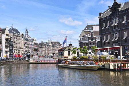 tour boats: Canal at Amsterdam city, Netherlands. Excursion boats and cityscape of Amsterdam at aa sunny day with blue sky. Tour boats on the canal and cityscape in the background. Editorial
