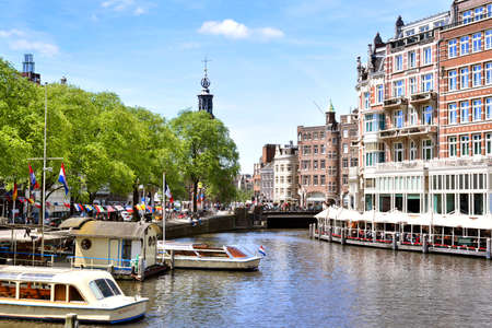 dyllic: Canal at Amsterdam city, Netherlands. Excursion boats and cityscape of Amsterdam at aa sunny day with blue sky. Tour boats anchored and idyllic restaurant Directly at the canal, with bell tower and cityscape in the background. Editorial