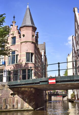 turret: Canal of Amsterdam with bridges and decorative cobblestone house with turret.