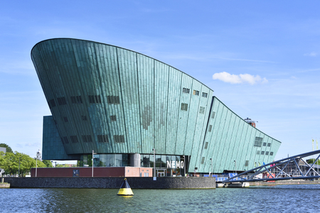 dutch culture: NEMO science center of Amsterdam. Maritime museum near Amsterdam Centraal Station. Futuristic building exterior at a sunny day in summer. Editorial