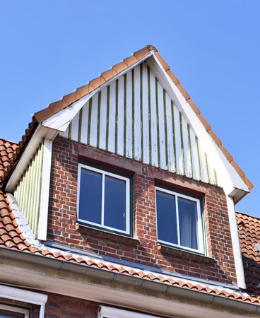 dormer: Old house with dormer. Architectural detail and blue sky. House with wooden dormer.