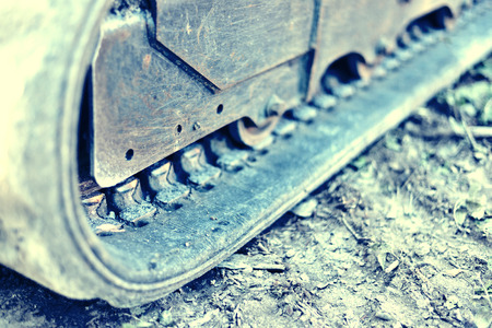 earthmover: Bulldozer or earthmover with selective focus and copy space. Heavy machine on a construction site. Close-up or macro shot of a caterpillar track.