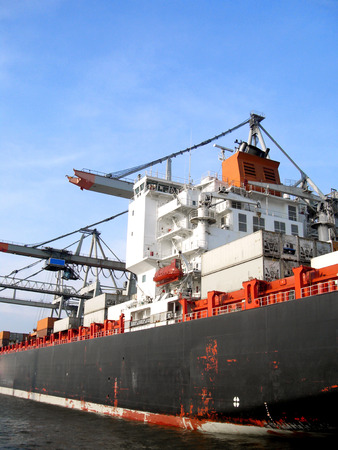 freight shipping: Freight shipping. Freight transportation. Hamburg harbor with on industrial ship anchored.