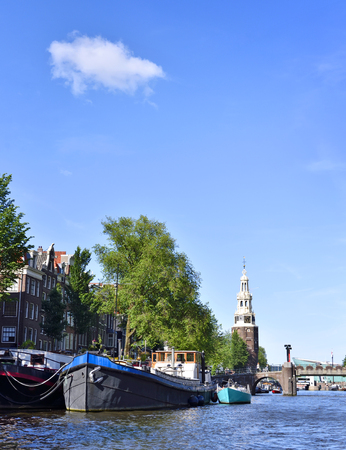 church tower: Amstel river with houseboats and view to on old church tower. Sunny summer day in Amsterdam city. Stock Photo