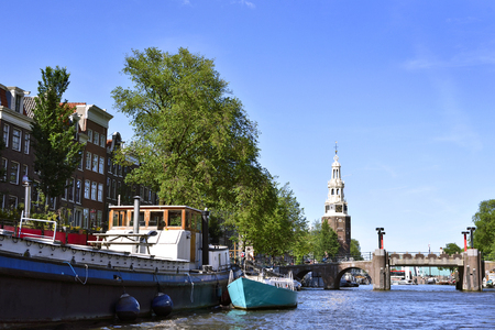 amstel: Amstel river with houseboats and view to on old church tower. Sunny summer day in Amsterdam city. Editorial
