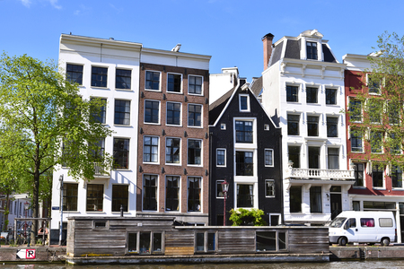 old houses: Amstel river, canal of Amsterdam with old houses and wooden houseboat. Fresh green trees and blue sky. Amsterdam in summer. Editorial