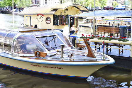 tour boats: Canal at Amsterdam city, Netherlands. Excursion boats and cityscape of Amsterdam at aa sunny day with blue sky. Tour boats anchored at the canal and cityscape in the background.