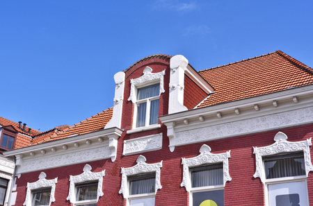 Old town house with dormer and stucco. Art nouveau house facade with decorative moulder and red cobblestones.