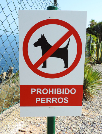warning back: Dogs prohibited sign. Spanish sign, no dogs allowed