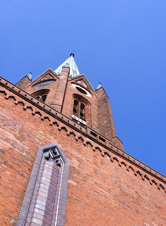church tower: Red cobblestone church in North Germany, Buxtehude. Old church tower with blue sky and copyspace.