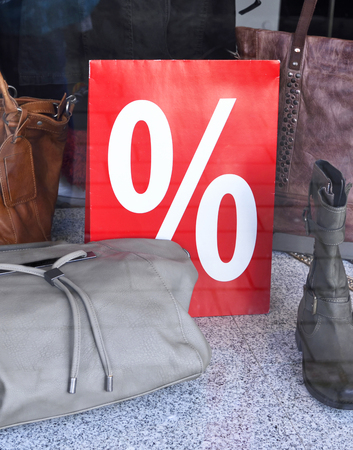 miserly: Sale in a clothes store. Percentage sign in a shop window.