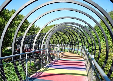 elevated walkway: Abstract bridge with metal rings and multicolored floor. Sunny day at Kaisergarten, Oberhausen.