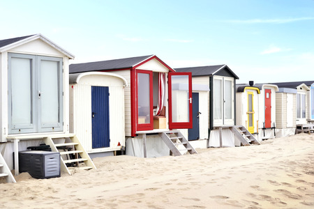 case colorate: Beach huts or houses and blue sky. Multicolored beach bathing huts with white sand and blue sky. Beach scene with copy space. Houses in a row.