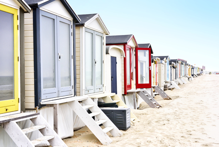 beach huts: Beach huts or houses and blue sky. Multicolored beach bathing huts with white sand and blue sky. Beach scene with copy space. Houses in a row.