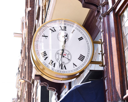 watch city: antique golden clock at a house facade. Antique watch shop in a historic city with elegant house facades. Time symbol. Stock Photo