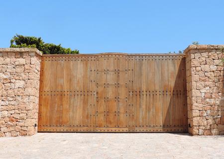 Holztor einer Villa mit Trockenmauer und Sicherheitssystem. Standard-Bild - 58501025